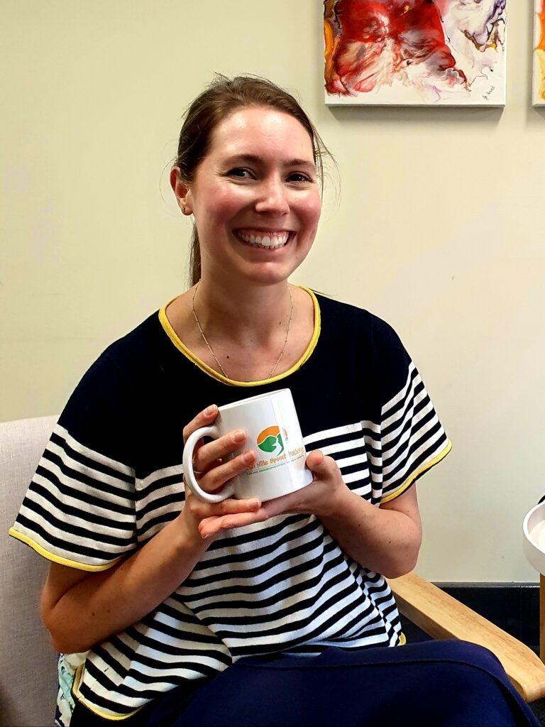 Speech Pathologist Charlotte smiling and holding a Perth Hills Speech Pathology coffee mug