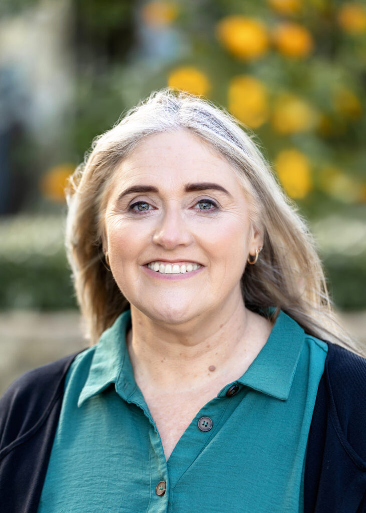 Image of Jackie. She is smiling and her long blonde hair is blowing gently in the breeze. She is wearing an aqua blouse and black jacket.