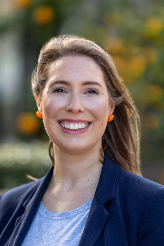 Image is of Charlotte. She is smiling. Her long hair is blowing gently behind her. She is wearing orange earings, a white blouse and a navy jacket.